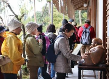 第2番札所の養仙寺で、境内の布袋像をなでる参加者たち(京都府亀岡市千歳町)
