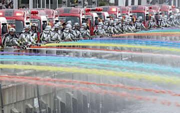 消防ポンプ車による色水の一斉放水=5日、大阪市住之江区のアジア太平洋トレードセンター