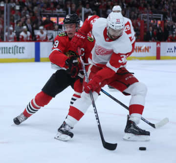 Chicago Blackhawks center Jonathan Toews (19) and Detroit Red Wings defenseman Brian Lashoff (32) battle in the first period on Sunday, Jan. 5, 2020 at the United Center in Chicago. - Chris Sweda/Chicago Tribune/TNS
