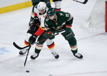Luke Kunin (19) of the Minnesota Wild keeps Mikael Backlund (11) of the Calgary Flames away from the puck during the first period on Sunday, Jan. 5, 2020 at Xcel Energy Center in St Paul, Minn. - Hannah Foslien/Getty Images North America/TNS