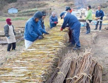 むいた楮の表皮の天日干し作業をする柴観光果樹農園組合の有志ら。手前にあるのが楮の木、右奥にあるのが切りそろえた楮の木を蒸す大釜=5日午前、東秩父村坂本地区