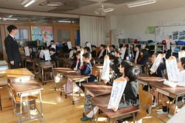 始業式後、教室で冬休みの宿題の書き初めを披露する児童=岡山市立鹿田小