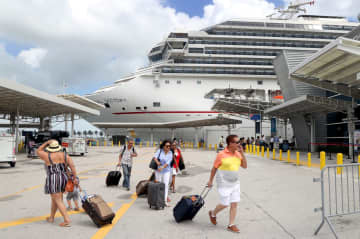 Passengers rush to board Carnival's Victory at the Port of Miami as they prepare to sail for Nassau. - Mike Stocker/Sun Sentinel/TNS