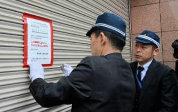 神戸山口組系の暴力団事務所に使用禁止の標章を貼る捜査員(7日午前10時2分、京都市南区)
