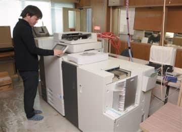ソフトウエアと印刷機を連携させ、ふるさと納税の業務を進める市職員。印刷機は自動で書類を束ねて封かんし、宛名書きまでを行う=荒尾市