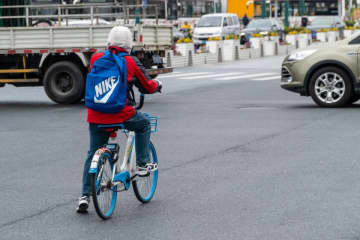 A Hellobike rider waits for traffic on the streets of Shanghai on March 22, 2019. (Image credit: TechNode/Eugene Tang)