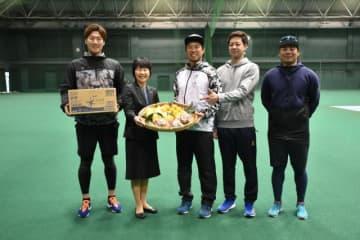 日向夏ミカンなど県産フルーツの贈呈を受け笑顔を見せる藤岡好明投手(中央)
