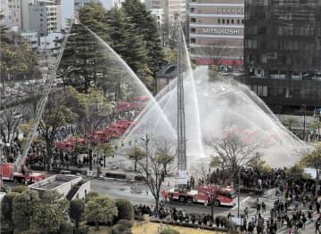 防火を祈願して行われたポンプ車やはしご車の一斉放水=7日午前11時55分ごろ、仙台市青葉区の勾当台公園市民広場