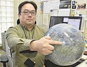 SLIMが着陸を予定している地点を月球儀で示す本田准教授。「安全な着陸と良質な科学データを観測できることを願う」と語る