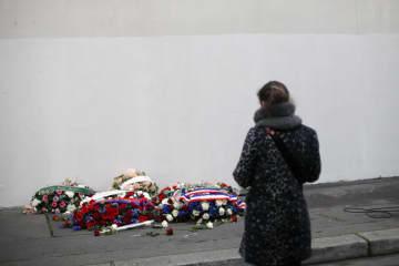 仏風刺週刊紙シャルリエブドの本社だった建物前に供えられた花と追悼する女性=7日、パリ(AP=共同)