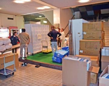 防疫ステーション設置に向け運び込まれたブルーシートや長靴などの資材を仕分けする県職員ら=7日午後7時すぎ、沖縄本島中部の体育館