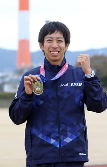 アジア選手権の銅メダルを手に、さらなる飛躍を誓う松尾。後ろは宮崎県延岡市のシンボルになっている旭化成恒富工場の煙突=旭化成陸上部グラウンド