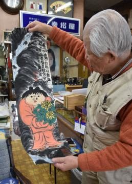 粛粲寶が使用していた机の中から出てきた作品「菊童子」を掲げる中山正男さん。表具後にギャラリーに展示する考えだ=境町