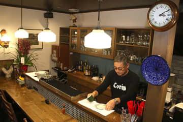 新しい店内で開店準備を進める細川昌之さん。照明や時計などは旧店舗で使ったものを再利用した=米沢市・カフェコリンズ