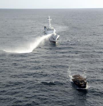 日本海の大和堆周辺で北朝鮮漁船(手前)に放水する海上保安庁の巡視船=2019年11月下旬(同庁提供)