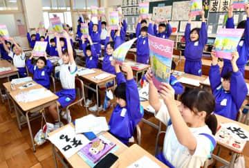 冬休みの宿題を掲げ、元気な笑顔を見せる児童たち=1月8日、福井県高浜町和田小学校