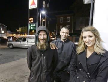 In this Nov. 2017, file photo, Johnny Bobbitt Jr., left, Kate McClure, right, and McClure's boyfriend Mark D'Amico pose at a Citgo station in Philadelphia (Elizabeth Robertson/The Philadelphia Inquirer via AP)