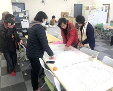 倉敷市真備町地区の地図を広げ、支援の在り方を話し合うメンバー