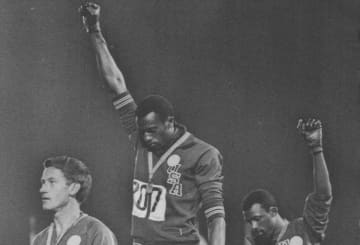 US bronze & gold medal winners Tommie Smith & teammate John Carlos famously raised their fists in a Black Power gesture during 1968 Olympic awards ceremony. Protest such as this will not be allowed at the 2020 Olympics. (Cleveland Plain Dealer/)