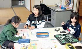 代替施設で宿題やボードゲームなどで遊ぶ子どもたち