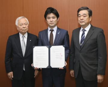 「タブレット図書館」の整備に向け、連携協定を結んだ(左から)熊本日日新聞社の河村邦比児社長と熊本県高森町の草村大成町長=10日、熊本市
