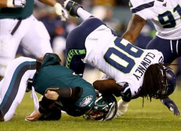 PHILADELPHIA, PENNSYLVANIA - JANUARY 05: Quarterback Carson Wentz #11 of the Philadelphia Eagles is hit by Jadeveon Clowney #90 of the Seattle Seahawks during the NFC Wild Card Playoff game at Lincoln Financial Field on January 05, 2020 in...