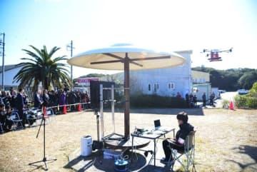 【ドローンを使った配送デモンストレーションを披露する楽天の担当者ら=志摩市の鵜方浜公園で】