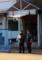 教官(右)の指導を受けてドローンを飛ばす練習をする受講生=佐用町豊福