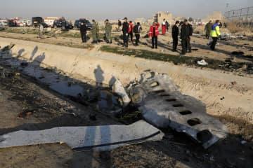 イラン・テヘランの空港離陸後に墜落したウクライナの旅客機の残骸と付近で活動する当局者ら=8日(AP=共同)