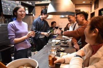 カウンターに立ち客の大学生たちと夢や展望を語る福島夏歩さん(左)ら=宮崎市