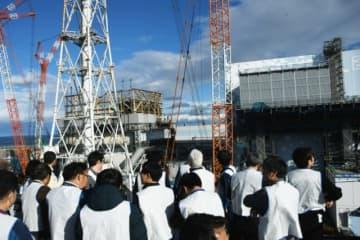 水素爆発で建屋の屋根が吹き飛んだ1号機(左奥)。右は2号機。いずれも使用済み核燃料やデブリは内部に残されたままだ=昨年12月、福島県の東京電力福島第1原発(代表撮影)