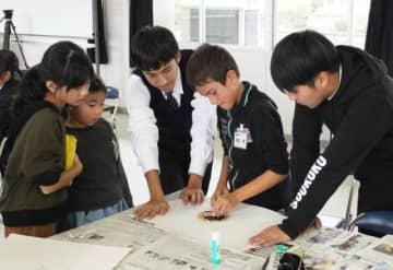 高校生のサポートを受けながら紙版画で鬼を作る児童=国東市国見町の竹田津小