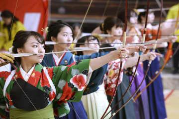 「通し矢」に由来する大的全国大会で、矢を放つ新成人たち=12日午前、京都市の三十三間堂