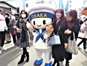まもるくんと記念撮影する参拝客=10日、大阪市浪速区