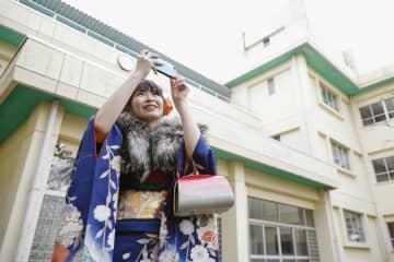 原発事故の影響で使われなくなった母校の小学校を訪れ、校舎を撮影する晴れ着姿の新成人=12日午後、福島県富岡町