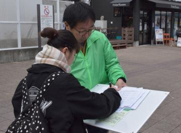 街頭署名活動を行う「いばらき原発県民投票の会」の鵜沢恵一共同代表=JR勝田駅前