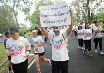 プラユット政権を批判し「タイの未来のために汗を流す」と書かれた紙を掲げながら走る参加者=12日、バンコク(共同)