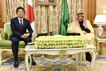 サウジアラビアのサルマン国王(右)と会談に臨む安倍首相=12日、リヤド(共同)