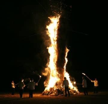 勢いよく燃えるトンド柱。来場者が巨大な火柱に願い事などを祈った=佐伯市の大入島