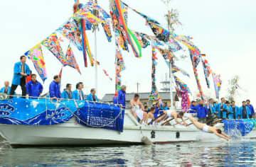 祝儀を受け取るために宝来船から桂川に飛び込むこぎ手=12日、豊後高田市