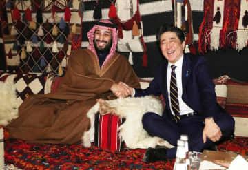 サウジアラビア・ウラー近郊でムハンマド皇太子(左)の歓迎を受け握手する安倍首相=12日(代表撮影・共同)