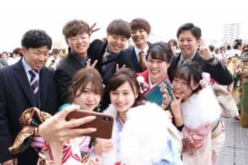 スマートフォンで旧友と記念撮影する新成人たち