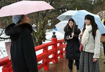 弘大留学生(右側)に下乗橋の由来について説明するガイド役の女性=11日、弘前公園内