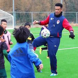 小学生とプレーする三都主アレサンドロさん=日岡山公園グラウンド