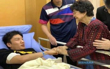 事故で顔を負傷し、病院でマレーシア首相夫人から見舞いを受ける桃田賢斗選手(左)=1月13日、クアラルンプール近郊プトラジャヤ(ベルナマ通信提供)