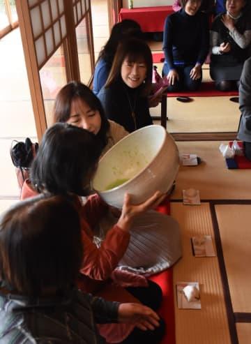 隣の人の手を借りながら巨大な茶碗でお茶を味わう参加者たち=唐津市肥前町の茶苑海月