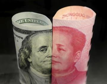 100ドル札(左)と100元札=2016年1月、北京(ロイター=共同)