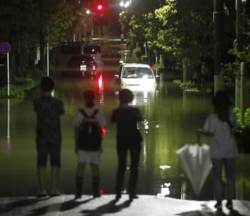 台風19号による雨がやみ、冠水した住宅地の道路を見つめる人たち=昨年10月12日、東京都世田谷区