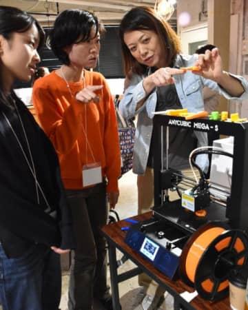 3Dプリンターで製作した自助具を説明する事業担当者(右)と参加者