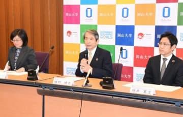 岡山大とUNCTADの包括連携協定について発表する槇野学長(中央)